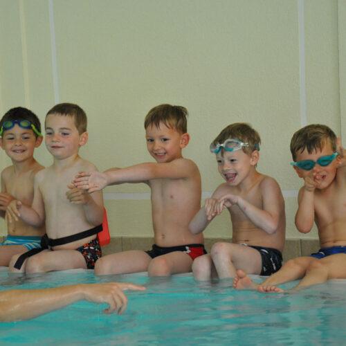 Auf dem Bild sind fünf Kinder bei einem Anfänger-Schwimmkurs zusehen. Sie sitzen am Beckenrand und machen die Übung nach, die ihnen vom Schwimmlehrer vorgezeigt wird.